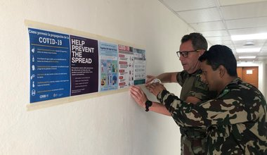 Comdt N Buckley SSO Media and Maj Sanjeev SO PR displaying COVID 19 Awareness posters in UNDOF HQ