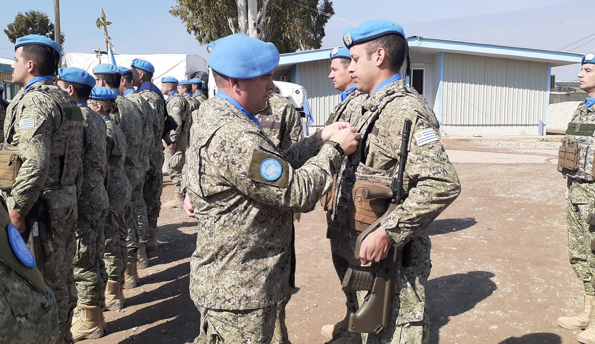 Chief Of Staff Col Martin Alvarez presenting Peace Keeping Medal to UMIC member.