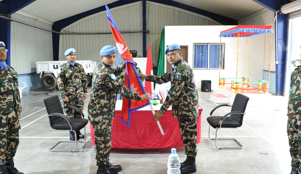 HANDOVER OF NEPALESE NATIONAL FLAG TO OUTGOING COMMANDER BY INCOMING COMMANDER