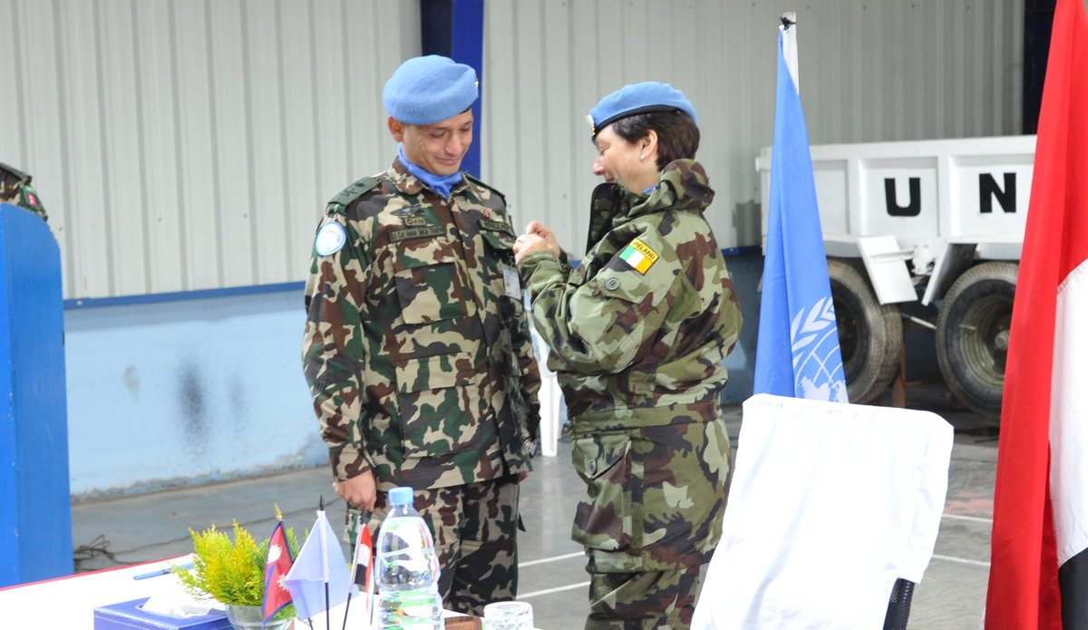 ACTING FORCE COMMANDER BRIG GEN MAUREEN O'BRIEN PROVIDING UNITED NATIONS PEACE SERVICE MEDAL TO OUTGOING NMC COMMANDER LT COL AMAR SINGH THAPA