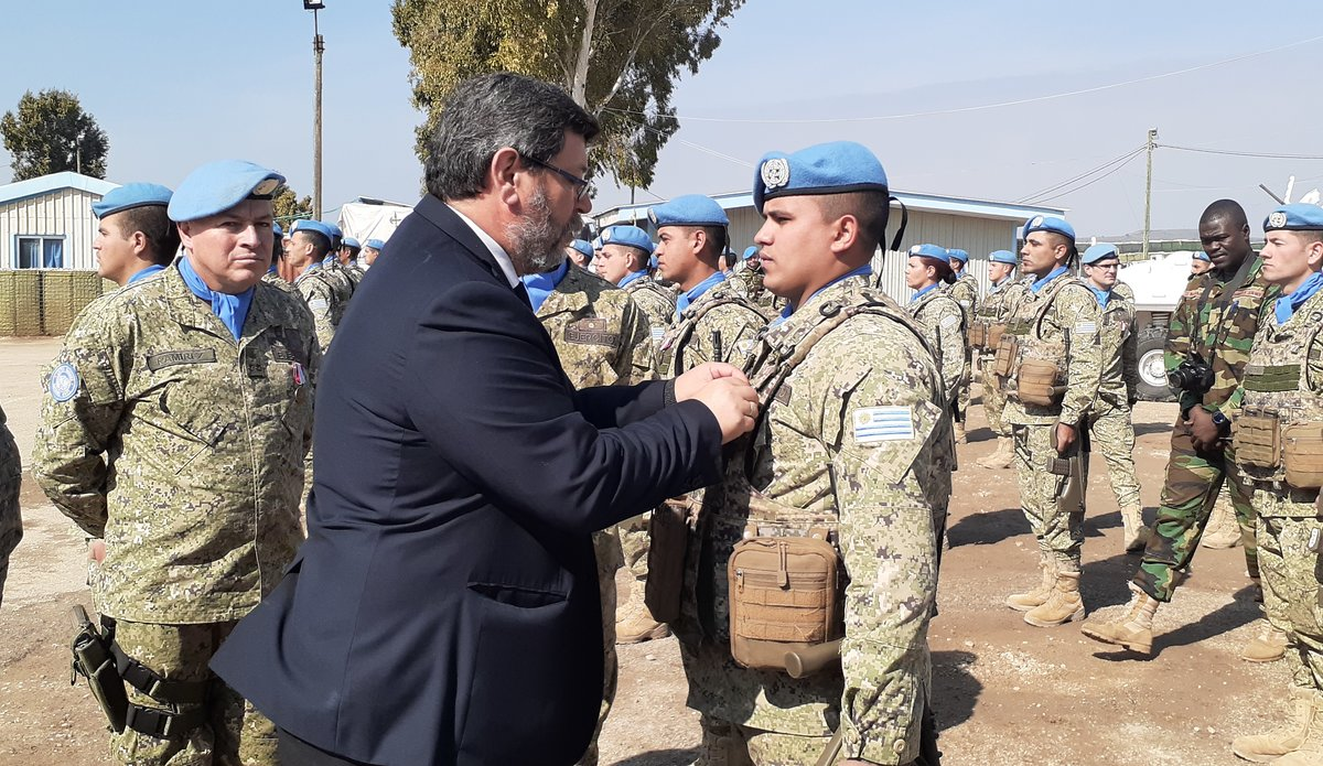 Deputy Defence Minister of the Uruguay Mr Berterreche Alvarez presents medals to Uruguayan peace keepers.