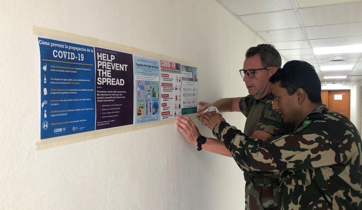 Comdt N Buckley SSO Media and Maj Sanjeev SO PR displaying COVID 19 Awareness posters in UNDOF HQ