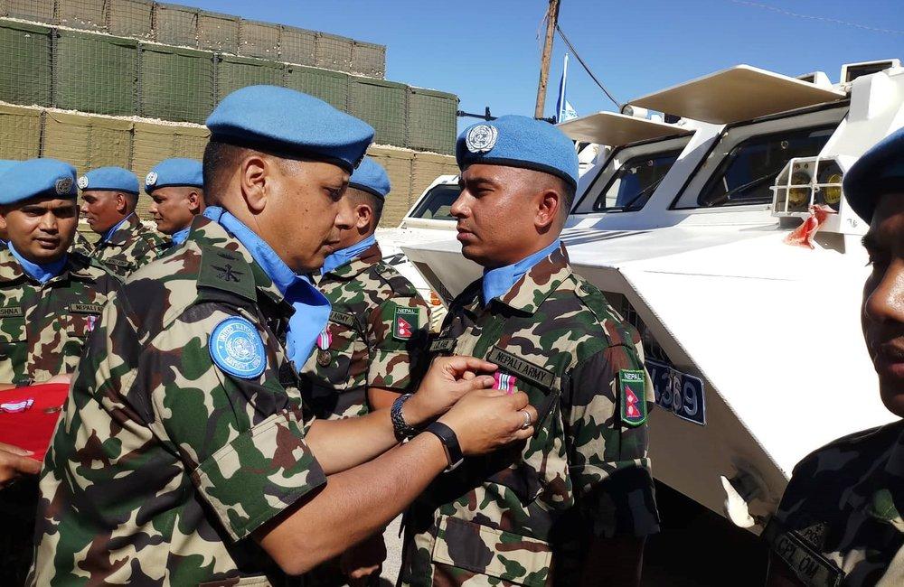 Lt Col Bijaya K.C. Officer Commanding NMC presents Medals to NMC Troops.