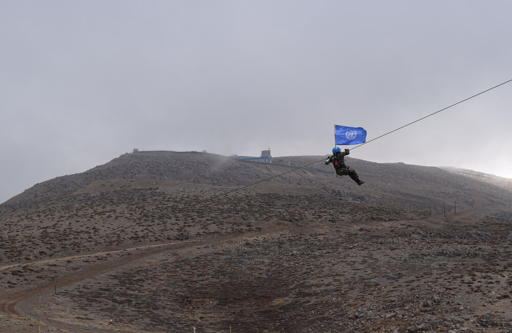 A NEPCON Mountain Troop slides down with the UN Flag