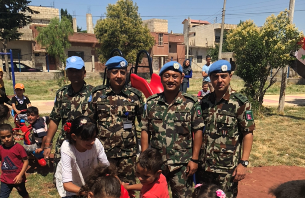 Lt Col Bijay O/C NMC with children and his staff at the opening of the new playground.