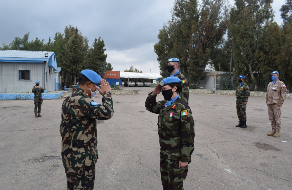 Force Commander taking the salute from the Deputy Force Commander after presenting her with her UN service medal