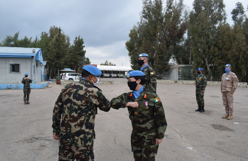 Force Commander 'shaking hands' with the Deputy Force Commander after presenting her with her UN service medal